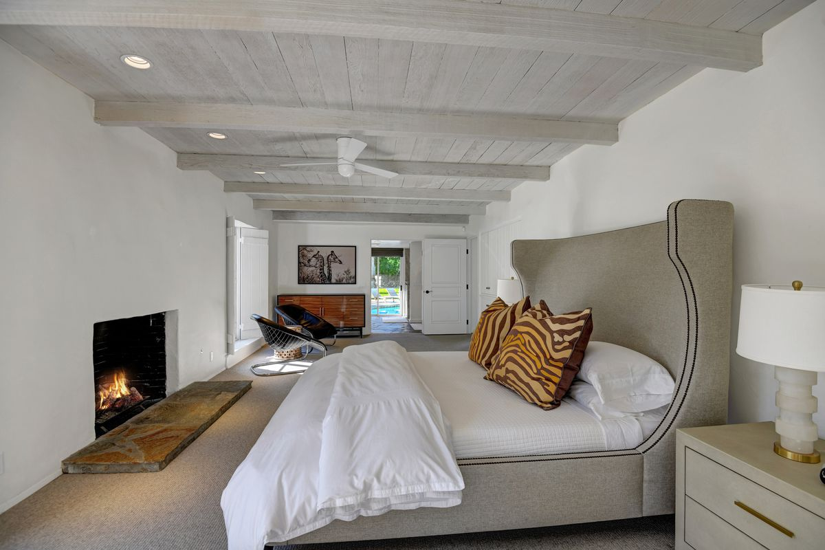 A bedroom has white ceilings and walls, a fireplace, and a large beige bed.