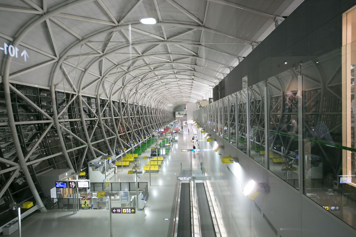 The interior of Kansai International Airport in Osaka. The walls and roof are curved and have steel beams running across them.