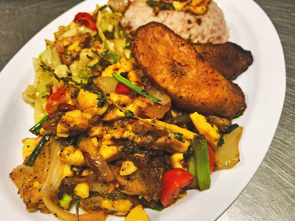 ackee, onions, peppers are seen on a plate next to fried plantain