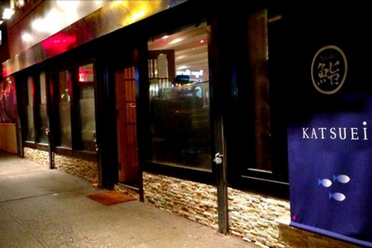 """A photograph of the front of a sushi omakase restaurant taken at night. To the right of the photo, a sign reads """"Katsuei."""""""