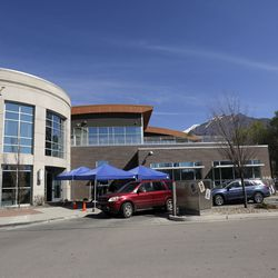 Cars line up for curbside pickup outside of the Springville Library in Springville on Wednesday, April 8, 2020.