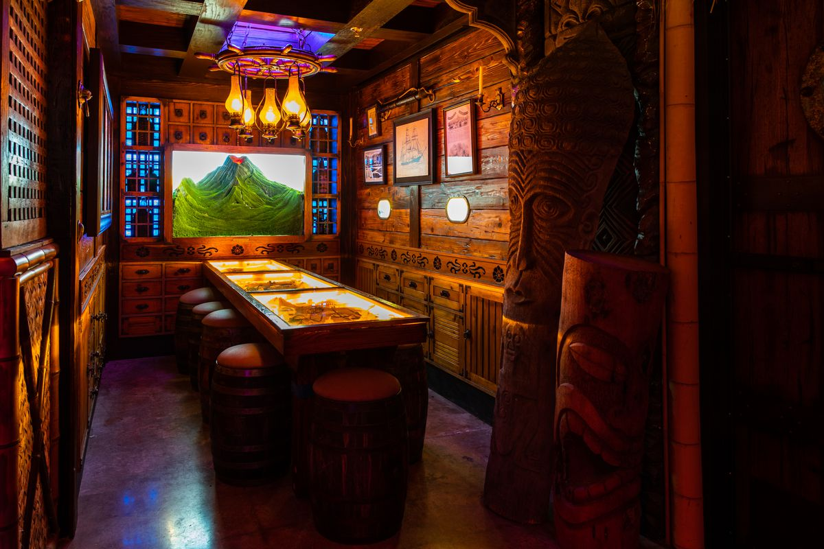 A wood-paneled room with a lit-up table and stools. An image of a green mountain hangs on the wall at the head of the table.