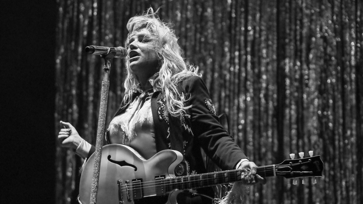 A black and white image of Kesha singing and playing the guitar