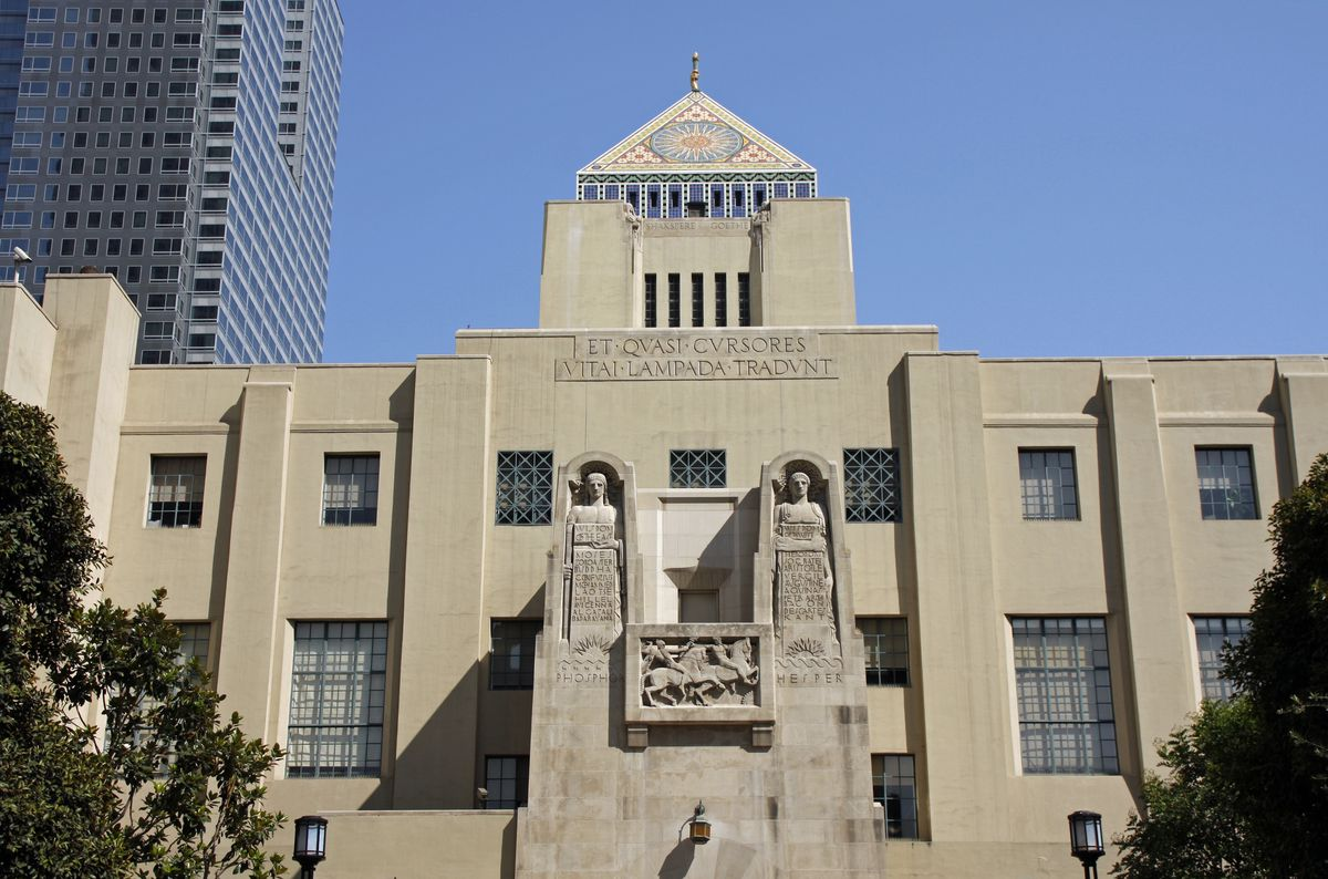 The exterior of the Los Angeles Public Library. The facade is tan and there are two statues of people above the entrance to the library.