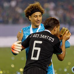 July 7, 2019 - Chicago, Illinois, United States - Mexico midfielder Jonathan dos Santos (6) kisses the Golden Glove award that Mexico goalkeeper Guillermo Ochoa (13) won during the Gold Cup Final at Soldier Field.