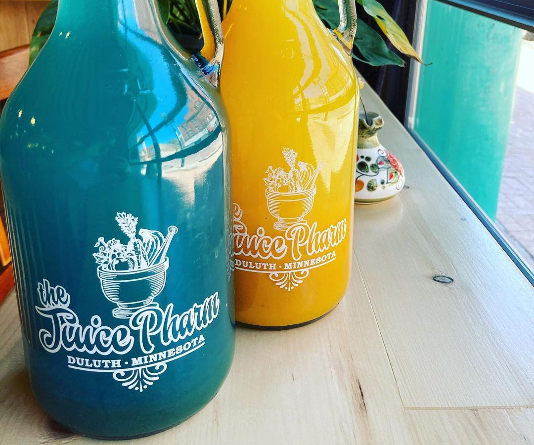 Two glass jugs, one filled with bright blue liquid and the other orange