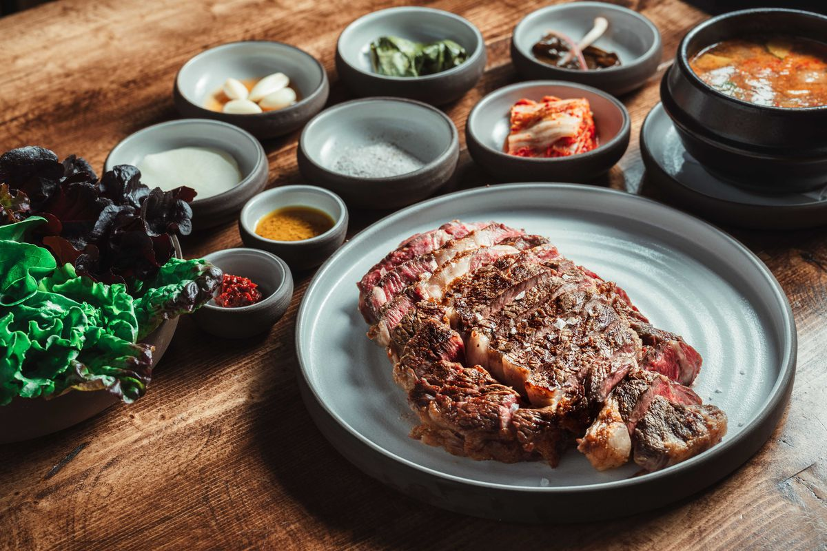 A sliced rare ribeye is on a gray plate on a wooden table. Small plates of Korean-style side dishes are visible in the background.