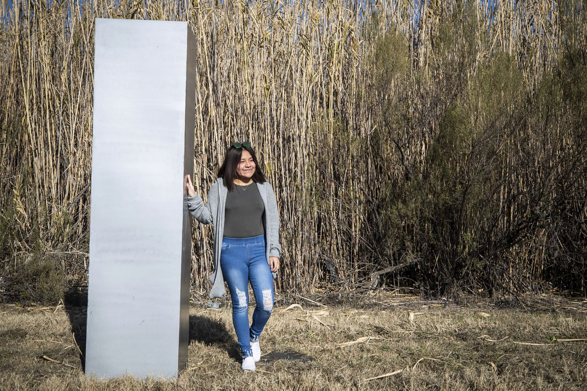 Roselyn Contreras poses for a photo by a metal monolith installed along the Trinity River on a trail off Beach Street, Tuesday, Jan. 12, 2021, in Fort Worth, Texas.