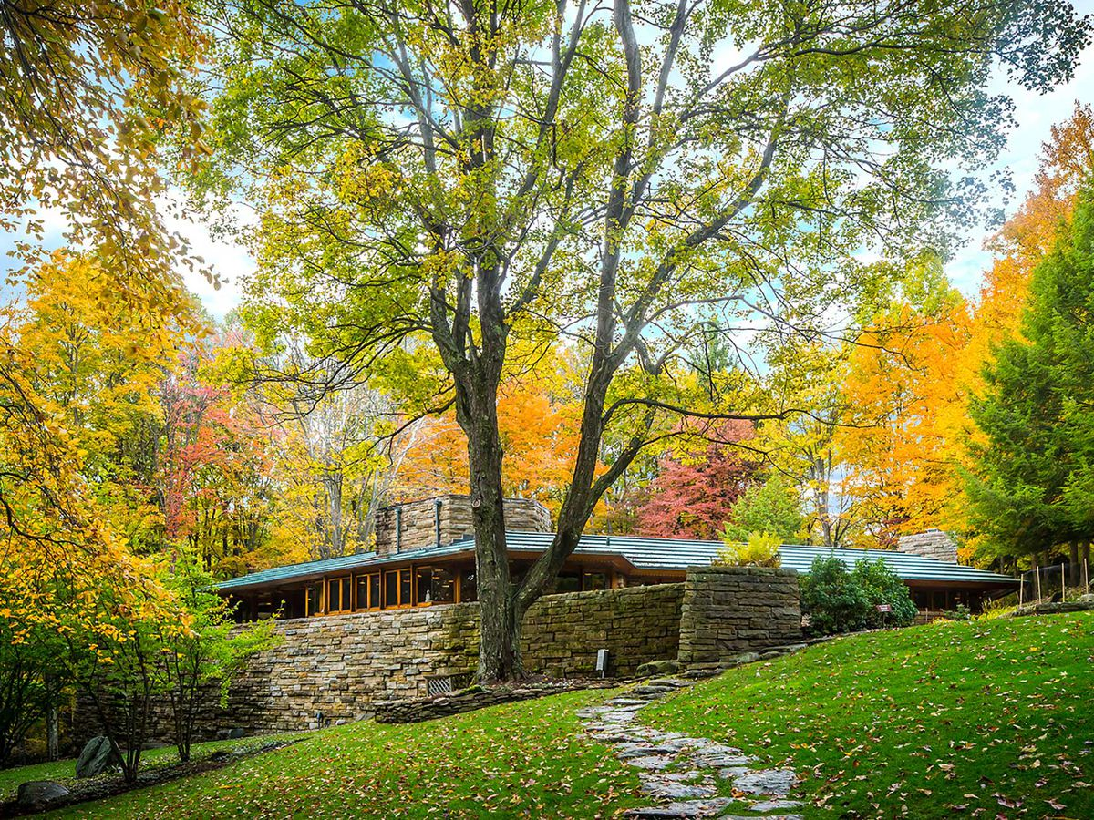 Kentuck Knob by Frank Lloyd Wright. The house has a stone facade with a grey roof. In the foreground is a path leading to the house. In the background are trees with multicolored leaves.