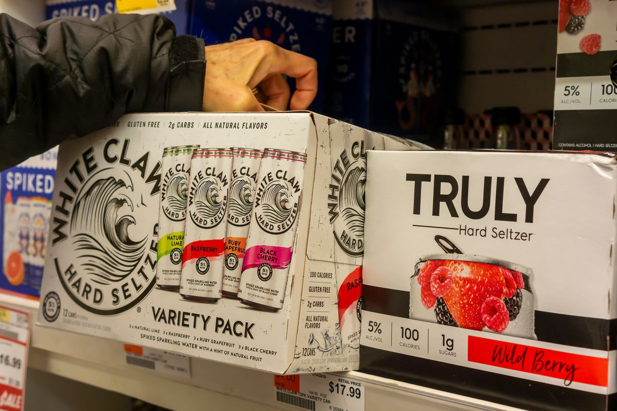 A person pulls a variety pack of White Claw spiked seltzer from a grocery store shelf