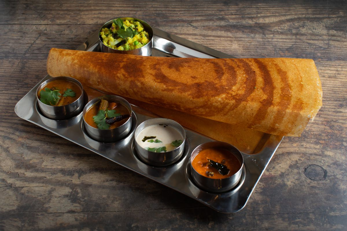 A long, thin dosa sits on a silver tray on a wooden surface. The tray also holds five small silver bowls of chutneys and sauces.