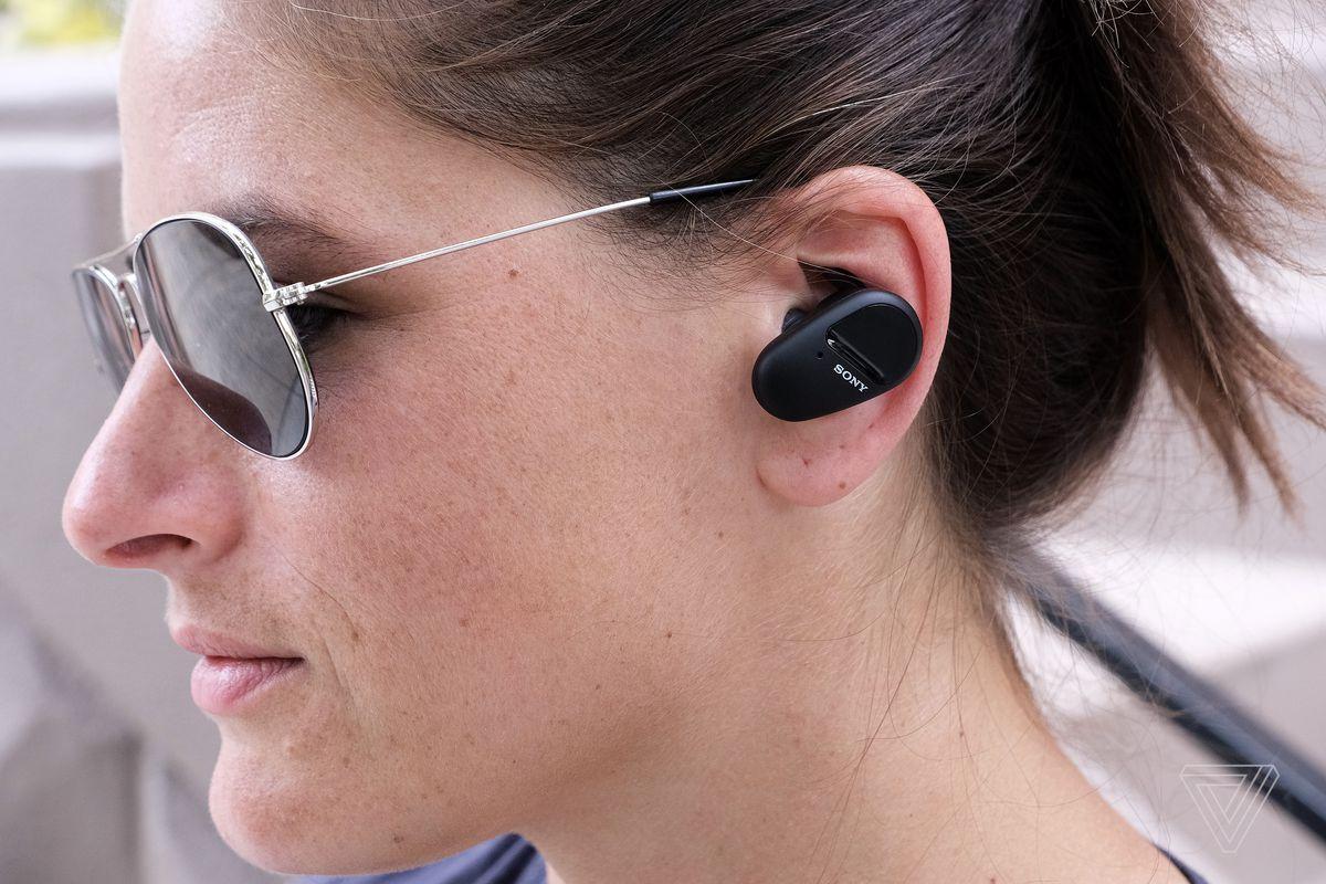 A side headshot of a woman wearing Sony's SP-800N earbuds.