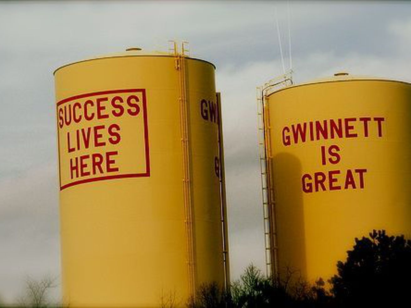"""Two yellow water towers in Gwinnett County. The one on the left shows text reading """"Success lives here,"""" and the one on the right reads """"Gwinnett is great."""