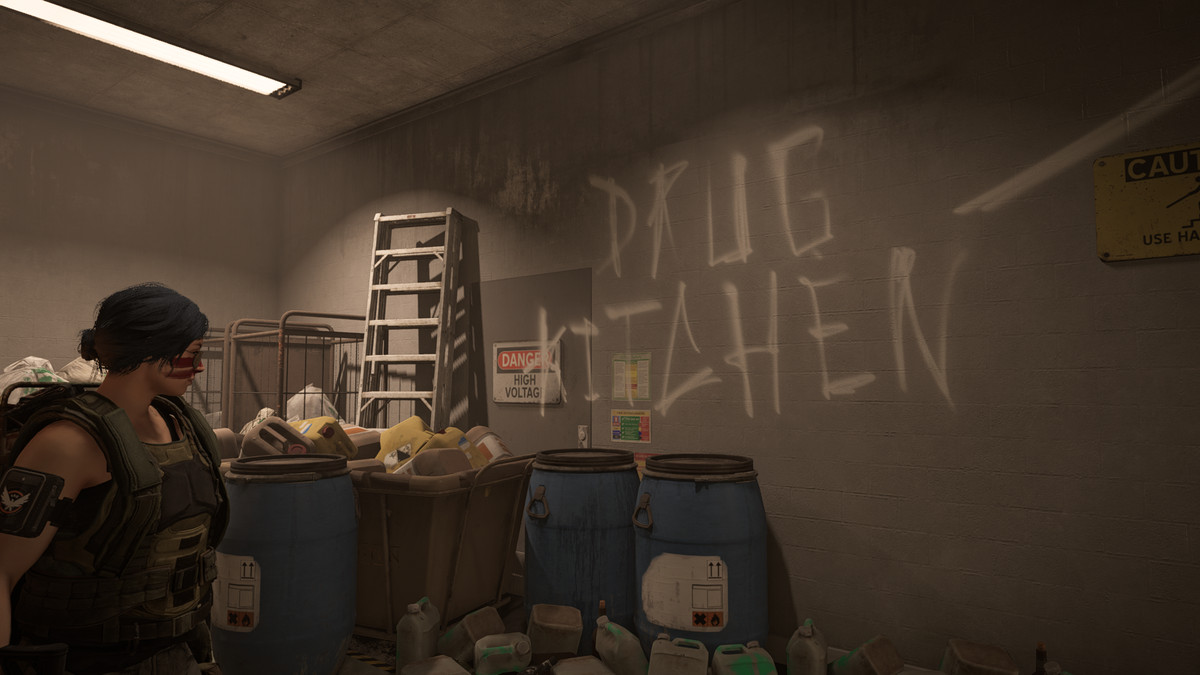 The Division 2 - a player character stands near a wall that reads drug kitchen