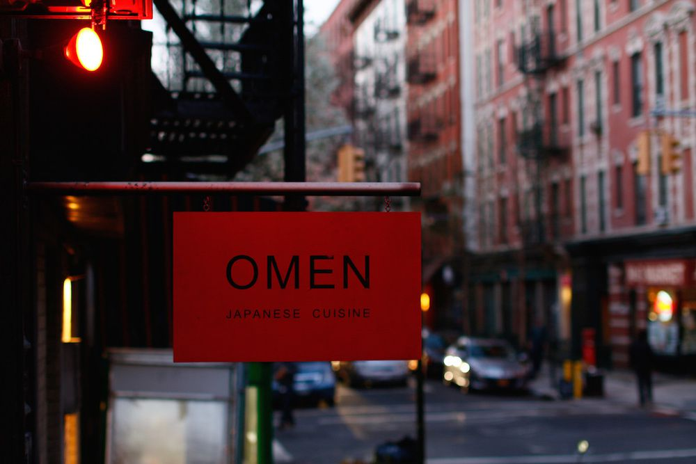 """A red signing reading """"Omen Japanese Cuisine"""" set against a city backdrop"""