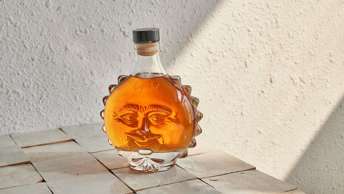 A bottle of tequila shaped like a son with a face