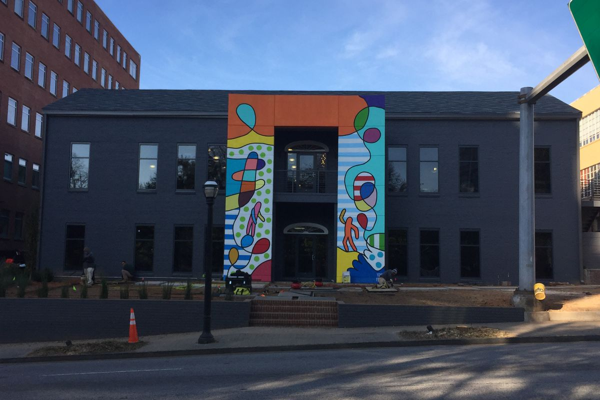 The main door of the slate grey building, framed by a two-story mural.