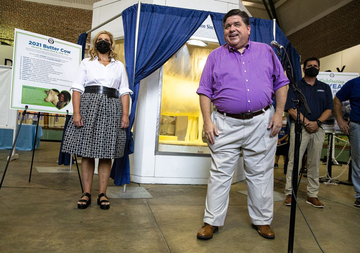 Gov. JB Pritzker and first lady MK Pritzker, left, unveil the 2021 Butter Cow at the Illinois State Fairgrounds on Wednesday.