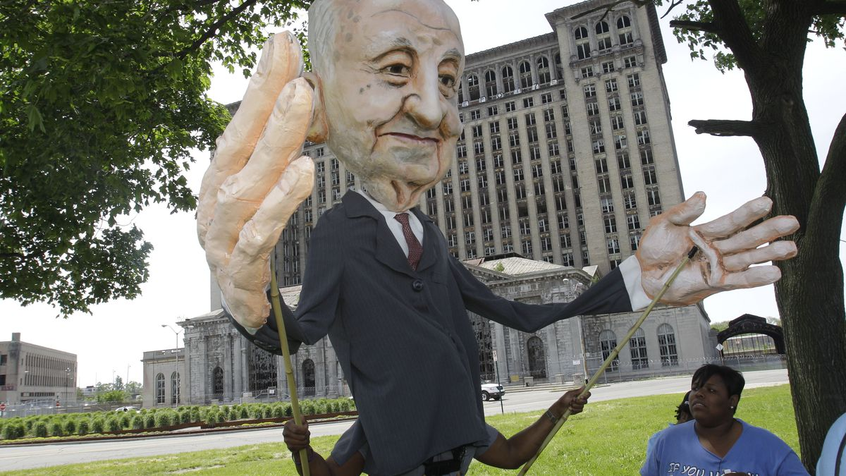 A person manipulates a large puppet of a white man in a black suite with several people watching nearby. Behind them is a large stone building.