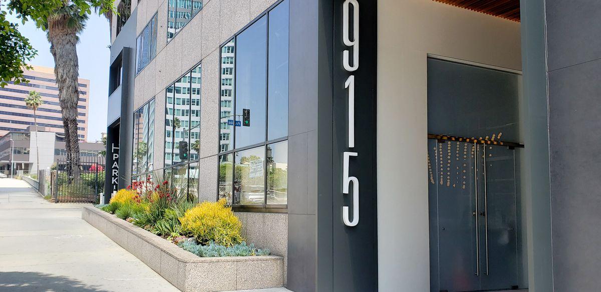 The corner entrance for a new restaurant along a slanted, sunny sidewalk.