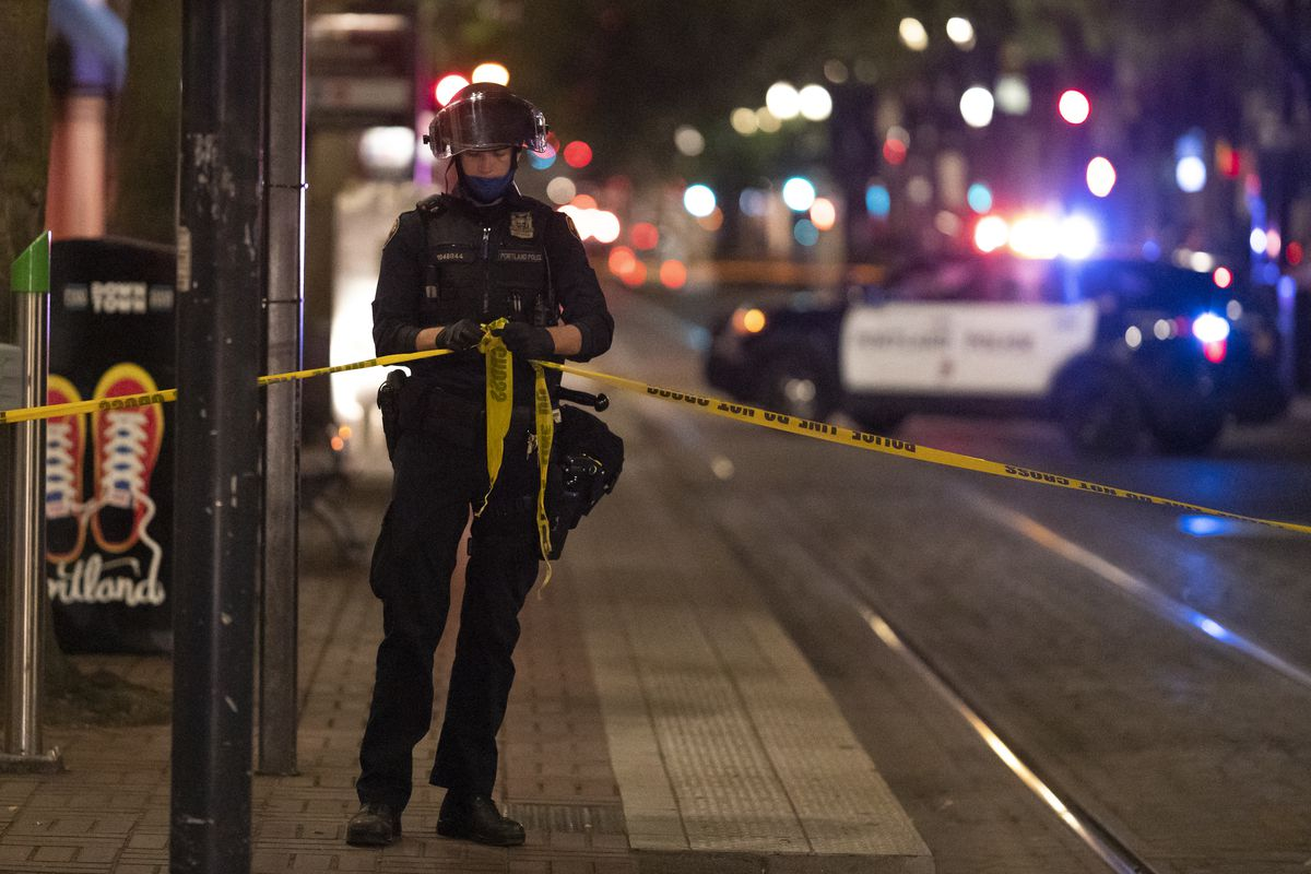 """The officer, in a riot helmet, face mask, and gloves, stands in front of a trash can featuring a illustration of red sneakers, their laces coiled to read """"Portland,"""" and ties two ends of yellow and black police tape together. Behind the officer, the red and blue lights of a police car flash."""