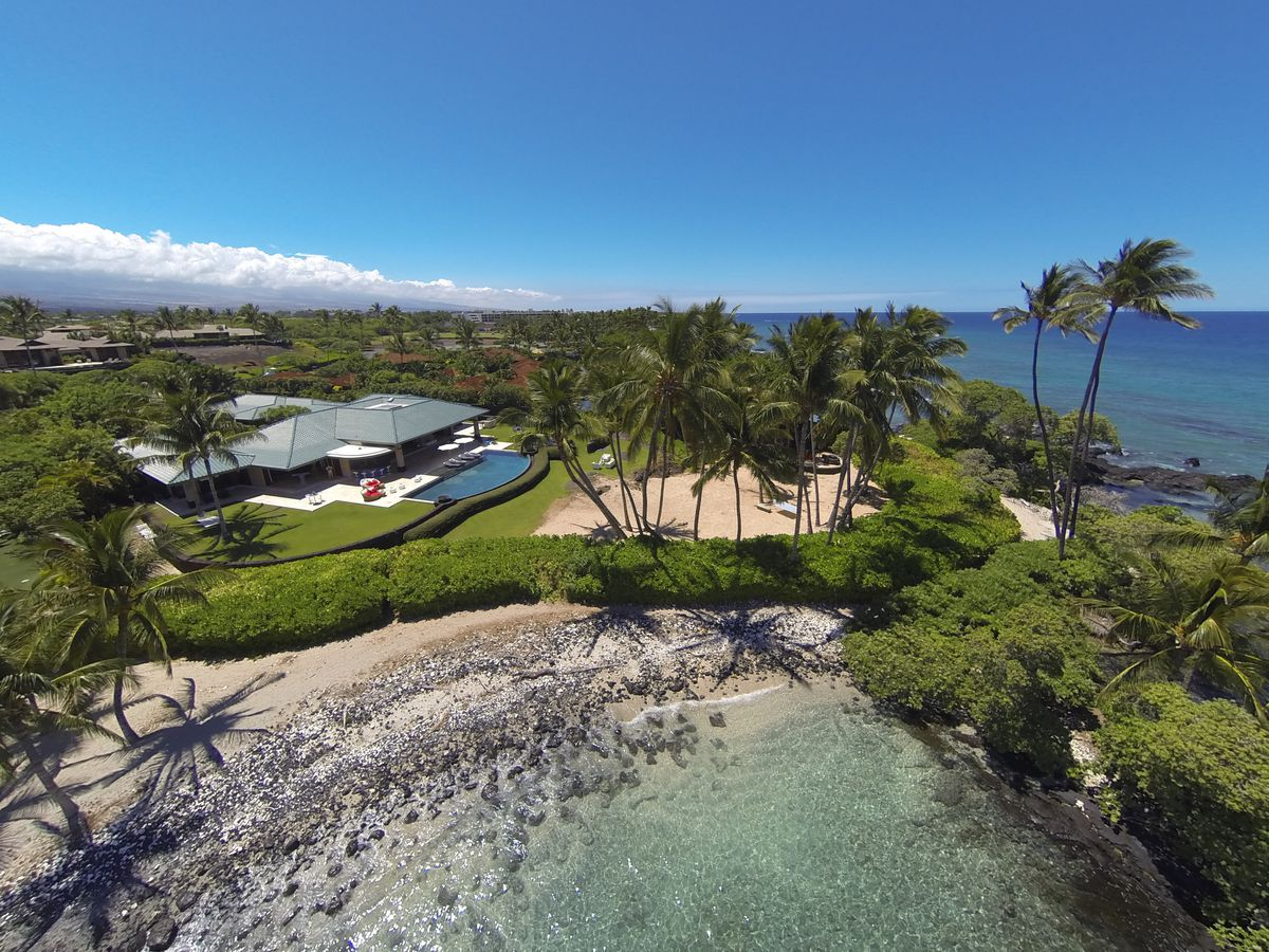 An aerial view of the home with the house on the left and a beach in front. Palm trees and vegetation surround the house.