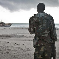 In this photo taken Sunday, Sept. 23, 2012, a Somali soldier looks out at a Taiwanese fishing vessel that washed up on shore after the pirates were paid a ransom and released the crew, in the once-bustling pirate den of Hobyo, Somalia. The empty whisky bottles and overturned, sand-filled skiffs that litter this shoreline are signs that the heyday of Somali piracy may be over - most of the prostitutes are gone, the luxury cars repossessed, and pirates talk more about catching lobsters than seizing cargo ships.