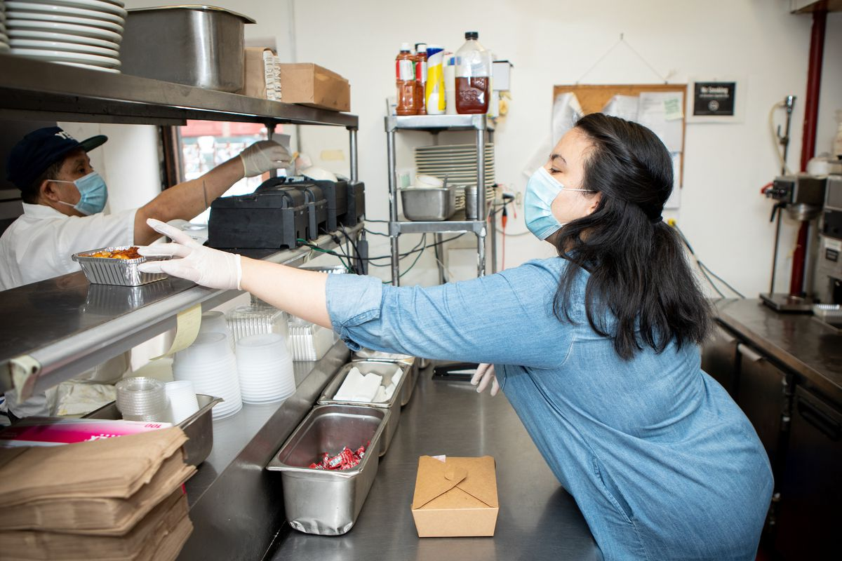 A woman in a restaurant kitchen reaches across the pass