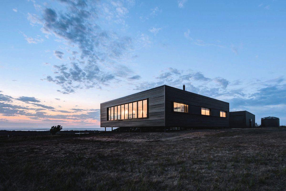 Cube-like home with black-clad exterior on rocky coastal terrain.