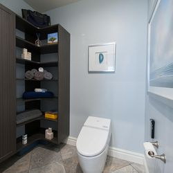 At the homeowner's request, this toilet room in the master bathroom, shown after renovation, was designed to accommodate a future walk-in tub. The required plumbing was installed behind the walls and floors to make future installation easy while in the meantime, the space is being used for storage.