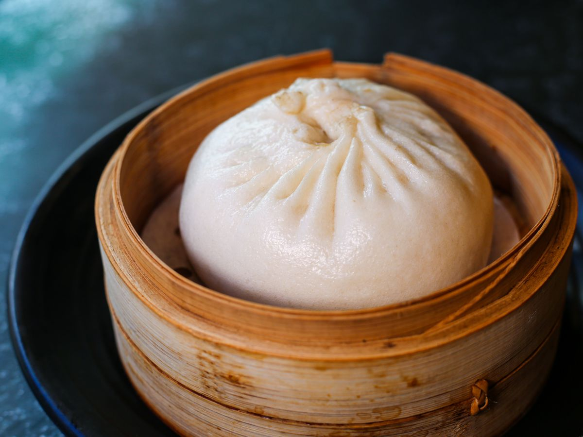 A close-up photograph of a steamed bun sitting in a wooden steamer basket