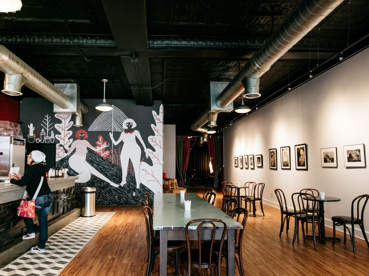 A coffee shop with a black and white interior and a mural with abstract mural of women in various poses.