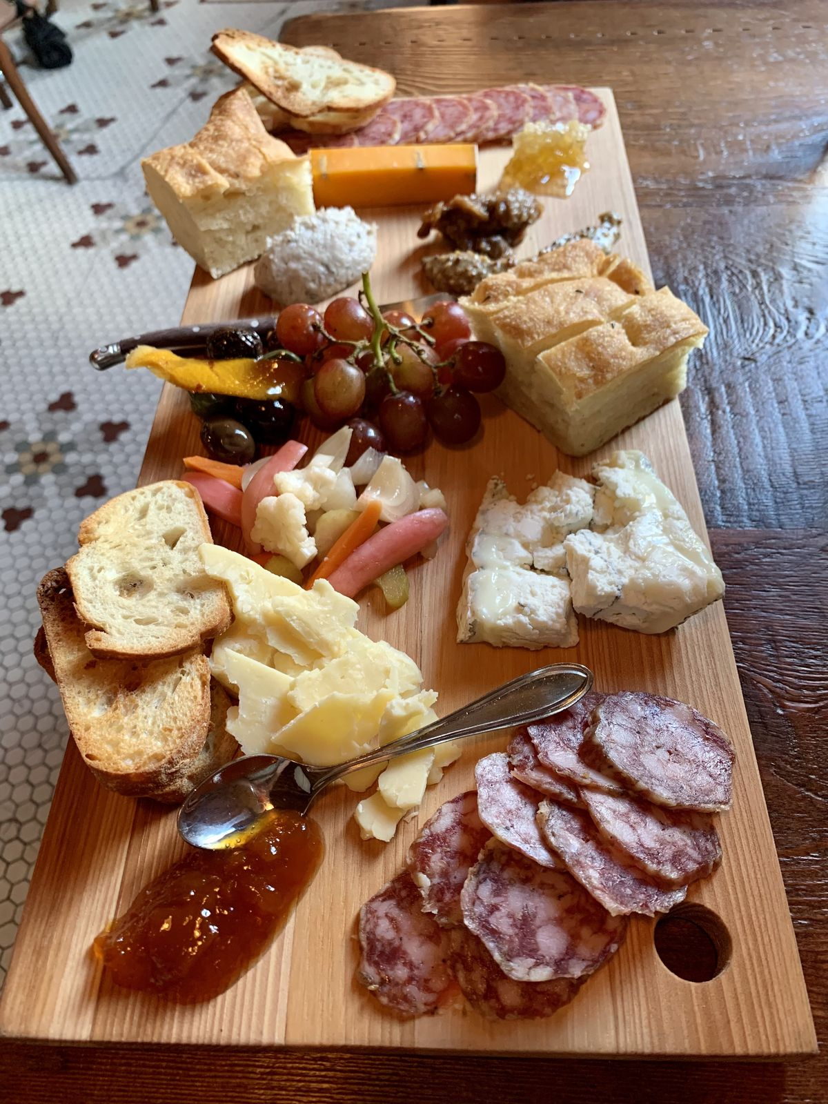 A wooden board filled with sliced meats and cheeses