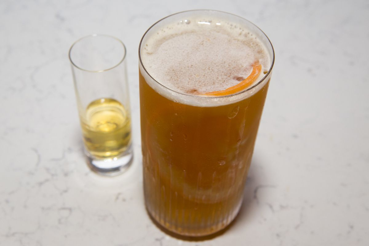 A tall glass filled with a brownish cocktail with orange slice and flanked by a shot of yellow-ish alcohol.
