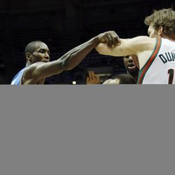 An official gets in the middle of Oklahoma City Thunders' Serge Ibaka, left, and Milwaukee Bucks' Mike Dunleavy during the first half of an NBA basketball game Monday, April 9, 2012, in Milwaukee.