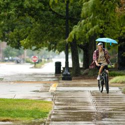 A cyclist holds an umbrella as he rides through the Purdue University campus in West Lafayette, Ind. as the remnants of Hurricane Isaac's rain falls on Sunday, Sept. 2, 2012.