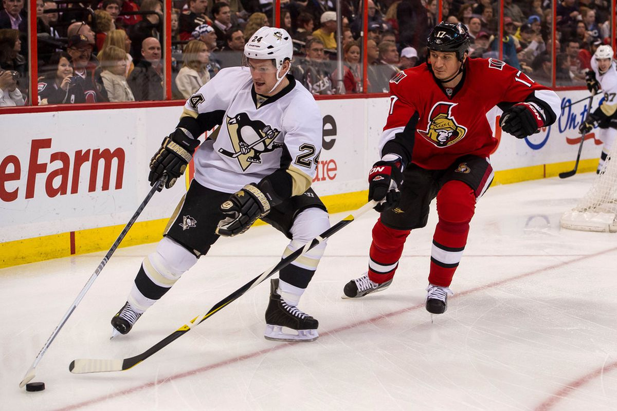 Mar 24, 2012; Ottawa, ON, CAN; Pittsburgh Penguins forward Matt Cooke (24) controls the puck as he is defended by Ottawa Senators defenseman Filip Kuba (17) in the first period at Scotiabank Place. Mandatory Credit: Marc DesRosiers-US PRESSWIRE