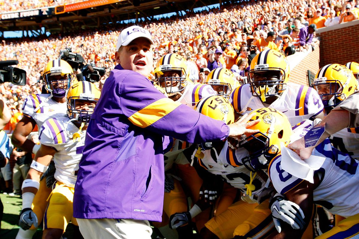 """KNOXVILLE, TN - OCTOBER 15:  Head coach Les Miles of the LSU Tigers leads his team in their usual pregame warmup song """"Head, Sheauxlders, Knees, and Teauxs."""""""