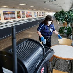 Pamela Adams cleans a seating area atSalt Lake City International Airport on Thursday, April 30, 2020. Like airports all over the world, Salt Lake's airport has seen air traffic plummet due to the COVID-19 pandemic.