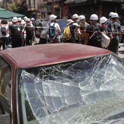 Lebanese youth who volunteered to help clean damaged homes and give other assistance, pass in front of a car that was damaged by last week's explosion, in Beirut, Lebanon, Tuesday, Aug. 11, 2020. The explosion that tore through Beirut left around a quarter of a million people with homes unfit to live in. But there are no collective shelters, or people sleeping in public parks. That's because in the absence of the state, residents of Beirut opened their homes to relatives, friends and neighbors.