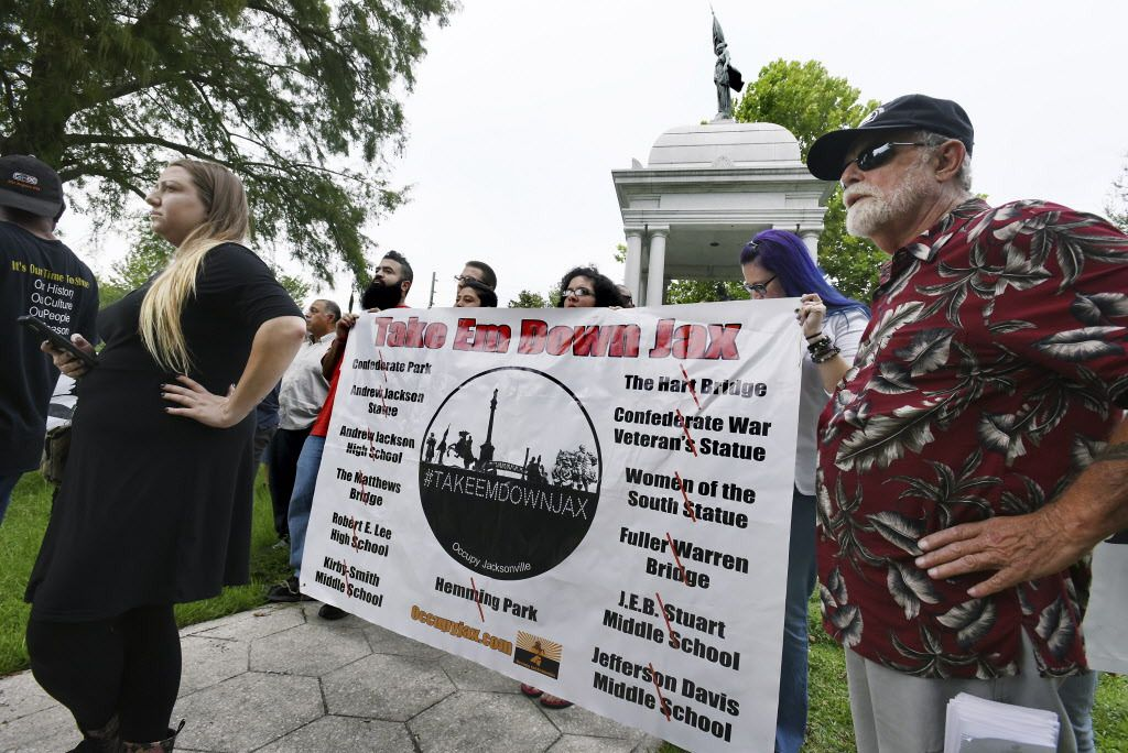 Members of the Take Em Down Jax organization hold a banner with the list of offending confederate monuments as well as buildings and locations they want renamed during a rally in Jacksonville's Confederate Park in Jacksonville, Florida, on Tuesday, Aug 15