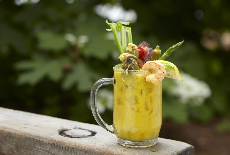 Light green drink in a glass mug with a garnish of shrimp, lemon slice, celery stalk, and assorted pickles.