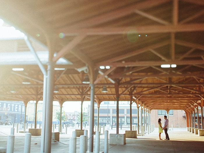 The interior of Eastern Market in Detroit. There is a ceiling with exposed wooden beams . A couple is holding hands and looking at each other in the distance.