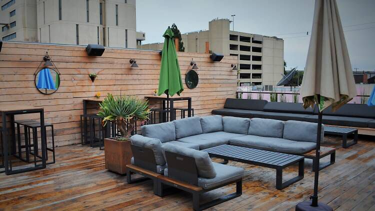 U-shaped patio couches sit on a wooden deck beside umbrellas, potted plants, and high-top bar tables with a city scape visible beyond