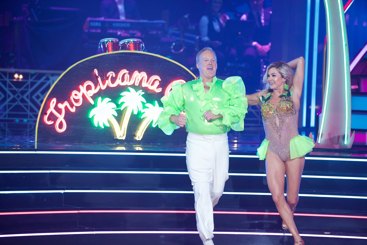 """Sean Spicer dancing with a partner onstage on """"Dancing With the Stars"""" with a neon Tropicana backdrop with palm trees."""