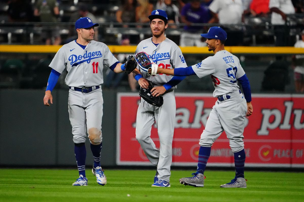 Los Angeles Dodgers left fielder AJ Pollock (11) and center fielder Cody Bellinger (35) and right fielder Mookie Betts (50) celebrate defeating the Colorado Rockies at Coors Field.