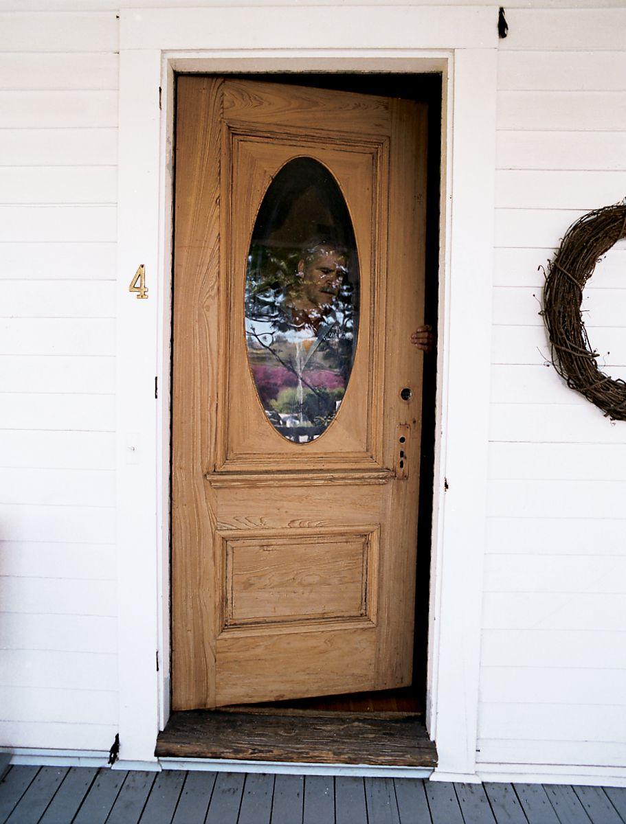 Man Seals Door Edges Before Rehanging Door