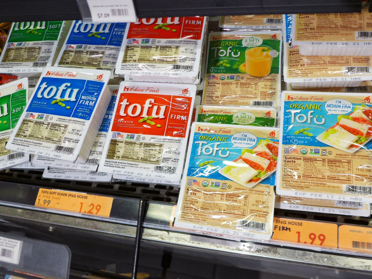 Colorful plastic packages of tofu in a Japanese refrigerator case.