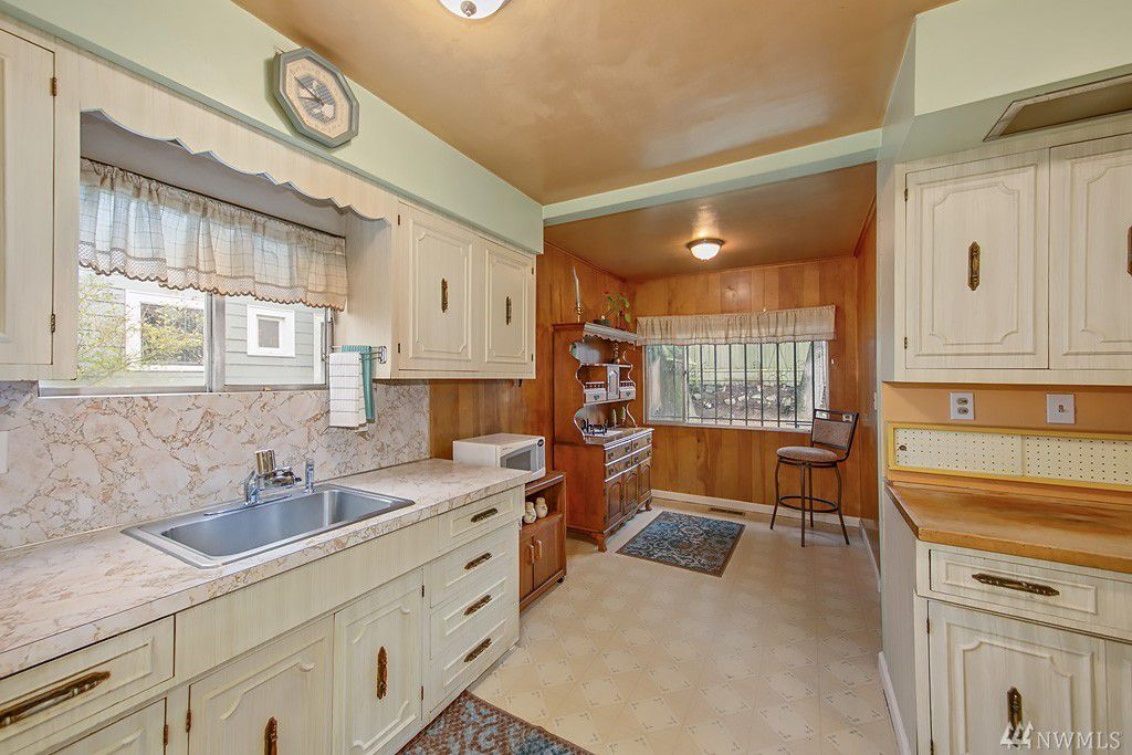 A kitchen with pastel mint top border paint and white woodwork, with a wood grain nook in the back.