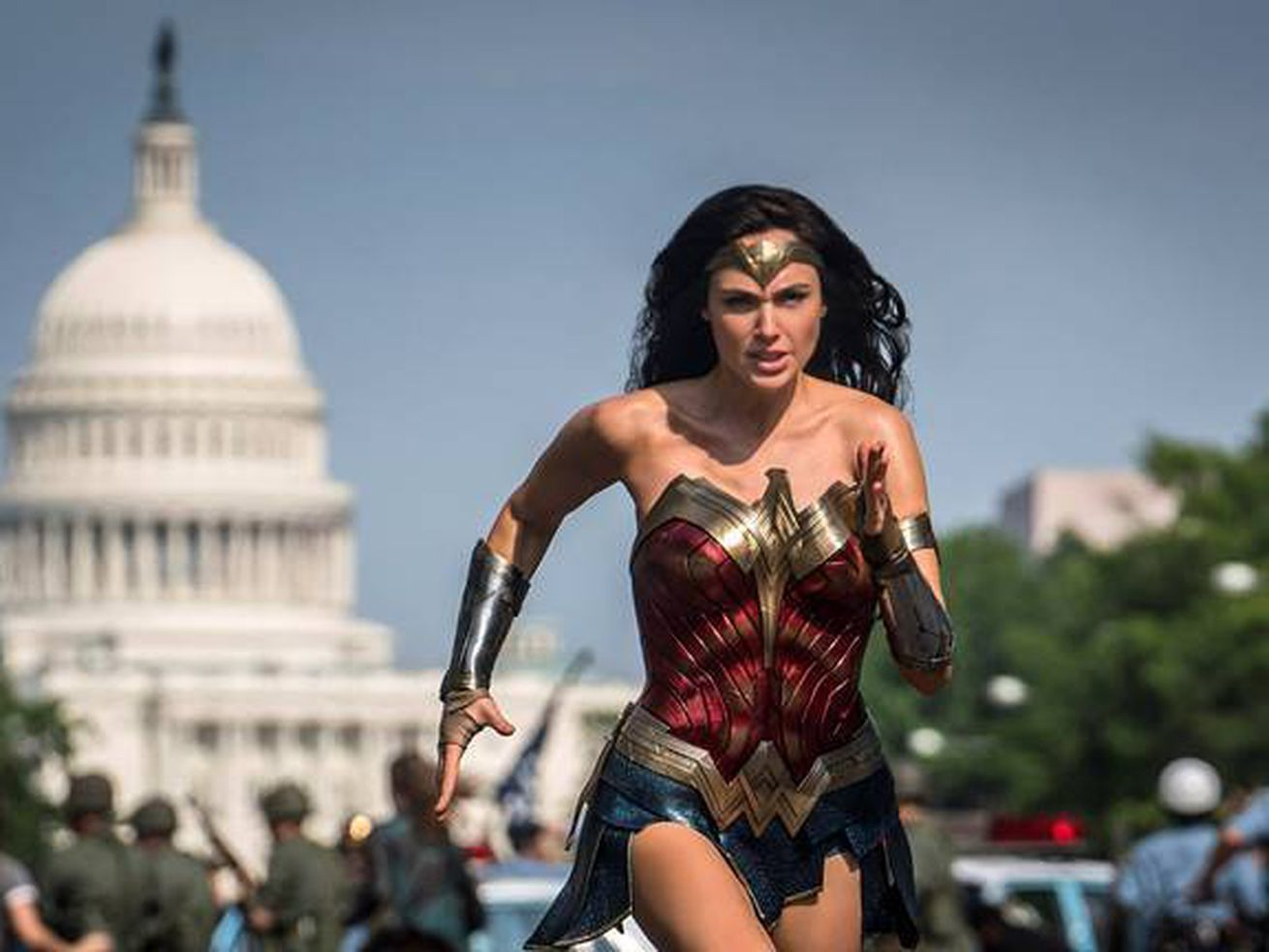 Wonder Woman running down a street in Washington, DC, with the Capitol building in the background.